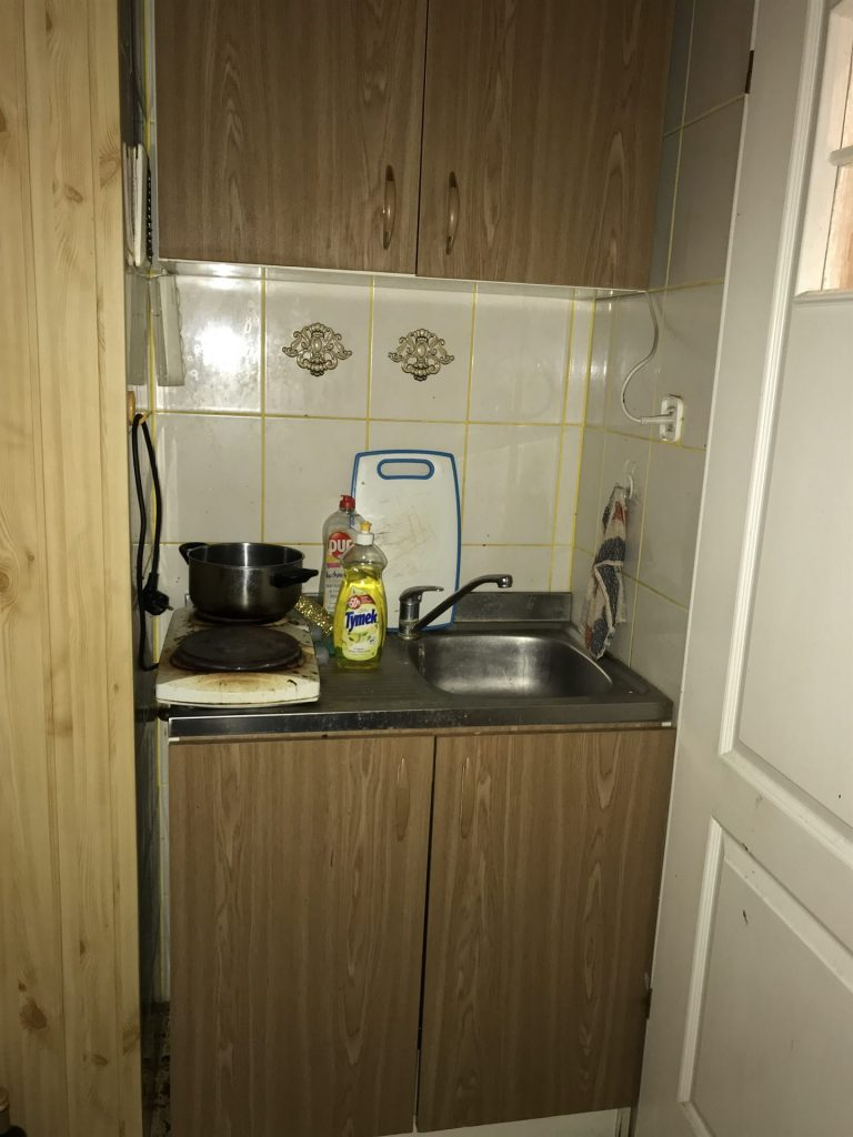 Mała kuchnia w mikroapartamencie przed home stagingiem w Warszawie
