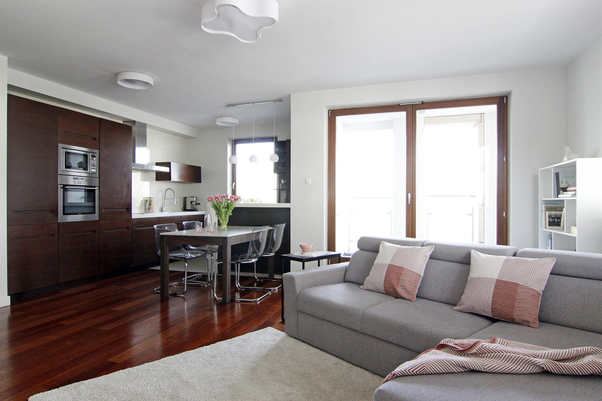 Home staging beżowego salonu z brązową kuchnią w mieszkaniu w Warszawie